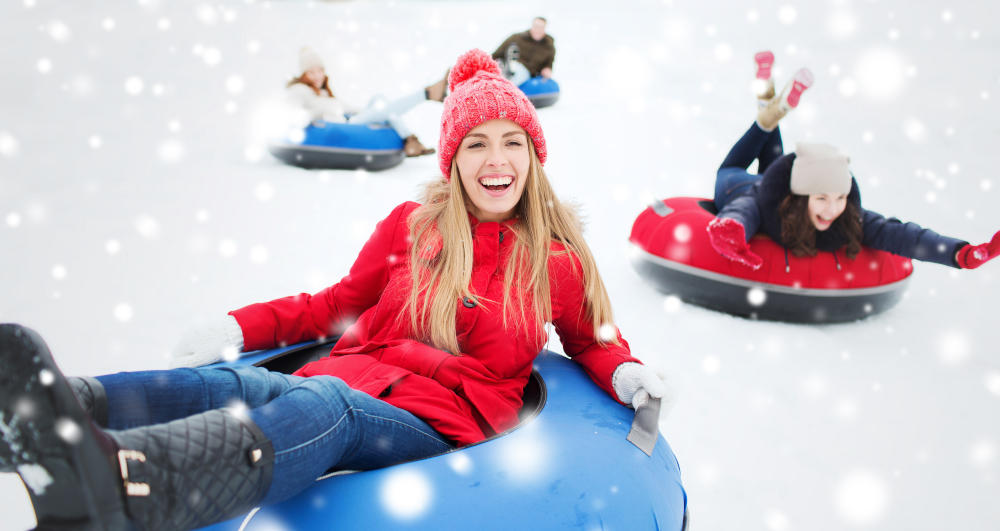 Eine Gruppe fröhlicher Mädchen beim Rodeln. Auch als Azubi stehen dir Urlaub und Feiertage für Erholung und Spaß zu!